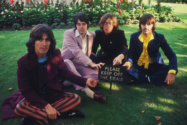 The Beatles sitting on the grass